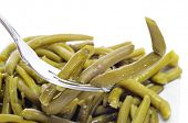closeup of a plate with cooked green beans on a white background
