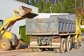 stock photo of oversize load  - Excavator scoops up a huge bucket and is about to empty it into the rear tray of the haulage truck - JPG
