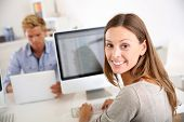 picture of worker  - Portrait of smiling office worker in front of desktop - JPG