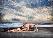 image of dreadlock  - Yoga parivrtta janu sirsasana pose by fit man with dreadlocks on the beach near the ocean at sunset background - JPG