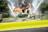 "image of safety barrier  - Empty ""do not cross"" tape with firefighters and a burning house in the background