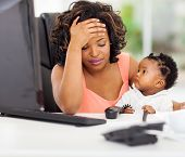 frustrated african american businesswoman with her little baby in office