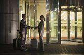 stock photo of late 20s  - Young business people handshaking outside of the office - JPG