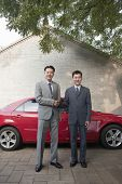 Two Businessmen Shaking Hands Next to Red Car