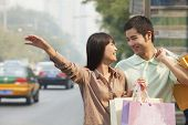 Young couple looking at each other with shopping bags hailing a taxicab in Beijing