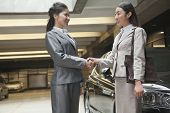 Two young businesswomen shaking hands in parking garage