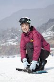stock photo of ski boots  - Smiling Woman adjusting Ski Boot in Ski Resort - JPG