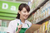 Sales Clerk Checking Groceries in Supermarket