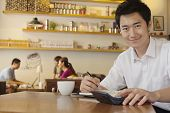 Portrait of young man working at a coffee shop