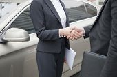Business People Shaking Hands By Car