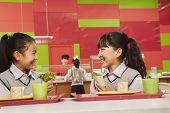 Two girls talking at lunch in school cafeteria
