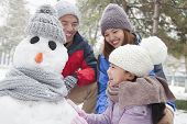 Family making snowman in a park in winter