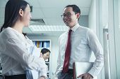 stock photo of button down blouse  - Businesspeople Talking at Work - JPG