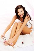 picture of nail-cutter  - Attractive woman cutting her nails in bed - JPG