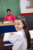 Portrait of beautiful teenage schoolgirl sitting at desk with teacher smiling in background