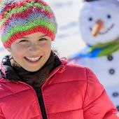 Winter play - beautiful girl and snowman, winter fun