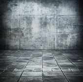 Dim concrete wall and floor space.