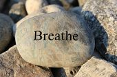 stock photo of breathing exercise  - Positive reinforcement word Breathe engrained in a rock - JPG