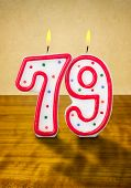 Burning birthday candles number 79 on a wooden background