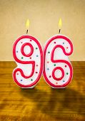 Burning birthday candles number 96 on a wooden background
