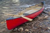 red canoe with a wooden paddle on a  shore of shallow fast river