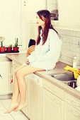 Young sad woman sitting on kitchen counter wearing men's shirt