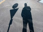 the shadow of a man on a sidewalk. anonymity of the big city.