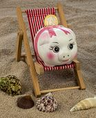 beach chair with euro currency on the sandy beach. symbolic photo for travel costs, holidays, vacati