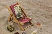 deck chair with dollars on the sandy beach. symbolic photo for travel costs, holidays, vacations. sa