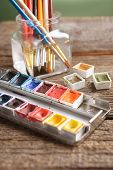 Professional watercolor aquarell paints in box with brushes in jar