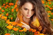 Beauty Romantic Girl Outdoors. Beautiful Teenage Model Girl  Posing Over Marigold Flowers Field. Enj