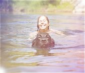 a girl and a big lab dog swimming in the water done with a retro