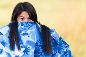 Playful young Thai girl peeking over the top of her blue umbrella or sunshade with an amused look as