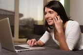 Attractive Woman Using A Mobile Phone And A Laptop