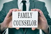 a man wearing a suit sitting in a desk with a desktop nameplate in front of him with the word family counselor