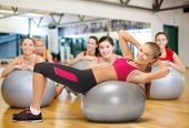 fitness, gym, exercise and health concept - young female instructor doing exercise on fitness ball i