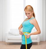 diet, sport and heath concept - beautiful sporty woman with measuring tape