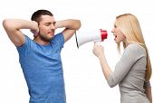 couple, family and relationship problems concept - girlfriend screaming though megaphone at his boyf