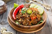 Mi goreng or mee goreng mamak, Indonesian and Malaysian cuisine, spicy fried noodles with wooden din