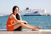 Young beautiful woman at the seaside in a resort town