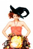 Beautiful red-haired witch casts a spell over pumpkins. Halloween. Isolated over white.
