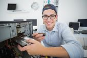 Smiling computer engineer working on broken console with screwdriver in his office