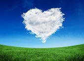 Cloud heart against green field under blue sky