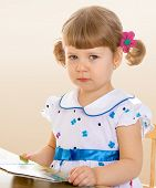 little girl sitting at the table.