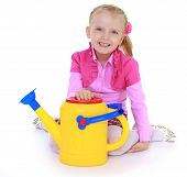girl holding a garden watering can.