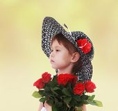 girl in a hat with a bouquet of flowers.