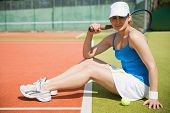 Pretty tennis player sitting on court smiling at camera on a sunny day