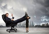 Young businessman sitting gin chair with legs on colleagues shoulders