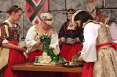 MUSKOGEE, OK - MAY 24: Women in historical costumes serve cake during the Queen's tea party at the O