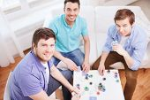 leisure, games, friendship, gambling and entertainment - three smiling male friends playing cards at